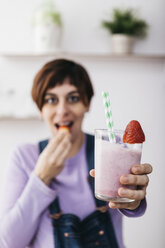 Woman holding glass of strawberry smoothie while eating a fruit - JRFF01239