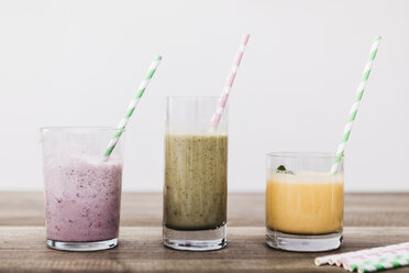 Three glasses of various smoothies in a row - JRFF01242
