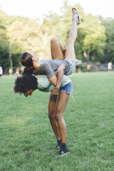 Young woman carrying her best friend piggyback in a park - GIOF01973