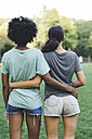 Back view of two women standing arm in arm in a park - GIOF01979