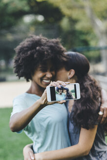 Two women taking selfiewith smartphone in a park - GIOF01985