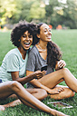 Two best friends sitting on a meadow of a park having fun with mini tablet - GIOF01994