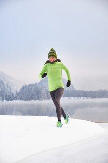 Germany, Bavaria, Lake Kochel, woman jogging in winter - MRF01689
