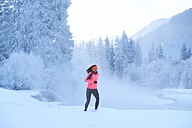 Germany, Bavaria, Isar valley, Vorderriss, woman jogging in winter - MRF01692