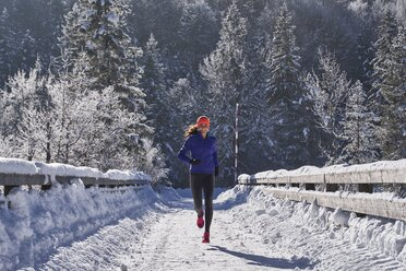 Germany, Bavaria, Isar valley, Vorderriss, woman jogging in winter - MRF01695