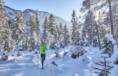 Germany, Bavaria, Isar valley, Vorderriss, woman jogging in winter forest - MRF01701