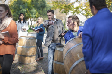 Wine salesman guiding wine workers with barrel outdoors - ZEF12880