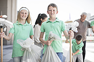 Group of volunteering children collecting garbage with litter sticks - ZEF12889