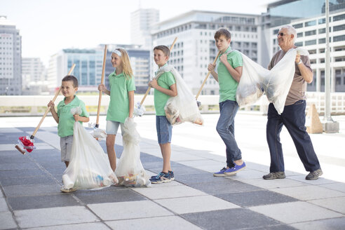Group of volunteering children collecting garbage with litter sticks - ZEF12892