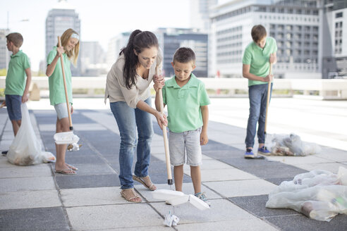 Group of volunteering children collecting garbage with litter sticks - ZEF12895