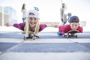 Kids skateboarding in the street, lying on belly - ZEF12907