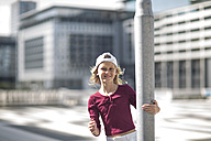 Smiling girl holding onto lamp post - ZEF12910