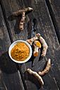 Whole and sliced turmeric, bowl of curcuma and an old knife on dark wood - CSF27889