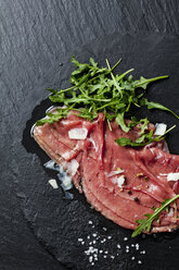 Beef Carpaccio with rocket, olive oil, parmesan, pepper and salt on slate - CSF27904