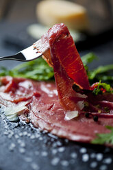 Beef Carpaccio with rocket, olive oil, parmesan, pepper and salt on slate - CSF27907