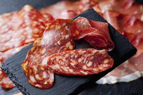Slices of Spanish salami and slice of Italian ham on slate - CSF27910