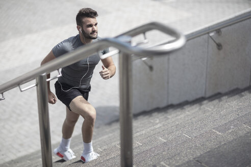 Athlete walking up stairs in the city - ZEF12915