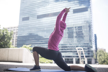 Young woman stretching on gymnastics mat in the city - ZEF12933