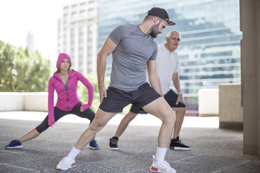 Three athletes stretching in the city - ZEF12942