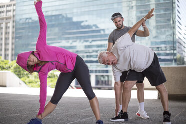Fitness instructor guiding senior man doing a stretching exercise - ZEF12945