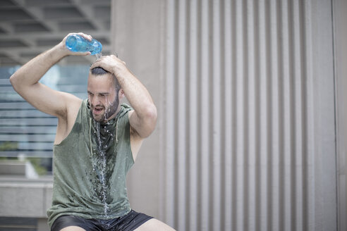 Athlete taking a break pouring water over his head - ZEF12954