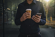 Businessman holding takeaway coffee and smartphone - KNSF01049