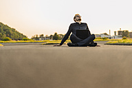 Businessman sitting on rural road with laptop - KNSF01055