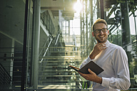Smiling businessman holding notebook in lobby - KNSF01070
