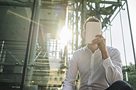 Businessman holding book in front of his face - KNSF01073