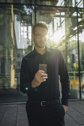Businessman holding futuristic portable device - KNSF01085