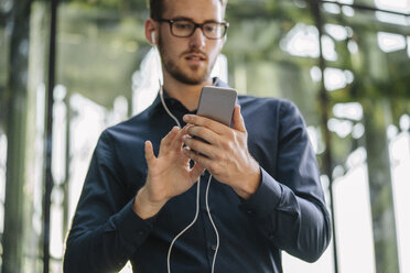 Businessman holding smartphone with connected earphones - KNSF01115