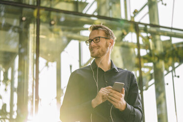 Smiling businessman using smartphone with connected earphones - KNSF01118
