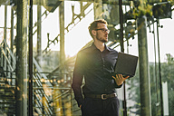 Businessman holding laptop outdoors - KNSF01121