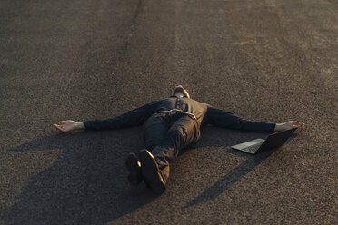 Businessman lying on a road next to laptop - KNSF01124
