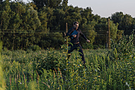 Businessman running with laptop in the nature - KNSF01127