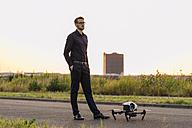 Businessman standing next to drone - KNSF01130
