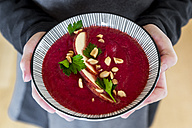 Girl's hands holding bowl of beetroot soup garnished with apple slices, peanuts and flat leaf parsley - SARF03209