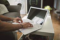 Young man sitting on couch, using laptop on coffee table - RAEF01743