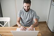 Young man sitting at home, using laptop - RAEF01746