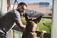 Young man standing at window with his dog, waiting - RAEF01749