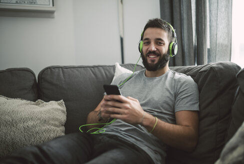 Young man sitting on sofa, listening music from his smart phone - RAEF01752