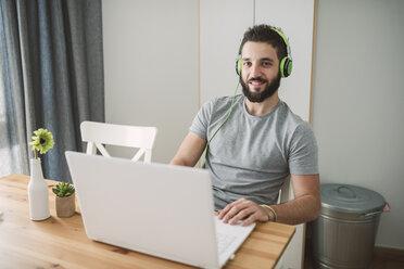 Young man wearing headphones, using laptop - RAEF01755