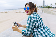 Young woman at the beach with cup of coffee and smart phone - GIOF02012