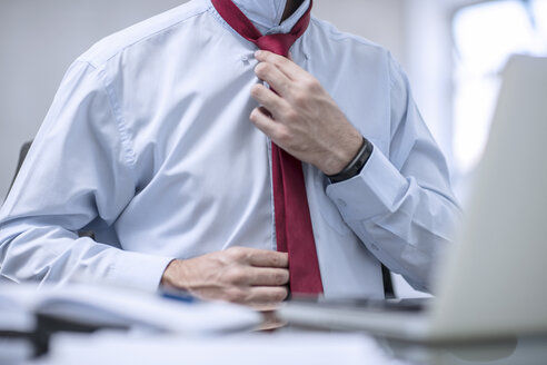 Person in office fixing his red tie - ZEF12970