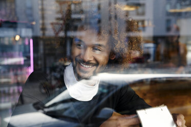 Portrait of smiling young man behind windowpane - FMKF03492