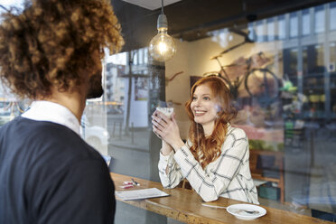 Man looking at smiling young woman in a cafe - FMKF03498