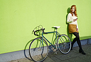 Young woman with cell phone lenaing against a green wall next to bicycle - FMKF03507