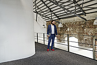 Businessman standing in office loft - FMKF03543