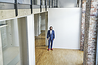Portrait of businessman standing on empty office floor - FMKF03546