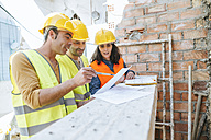 Woman and two construction workers talking on construction site - KIJF01240